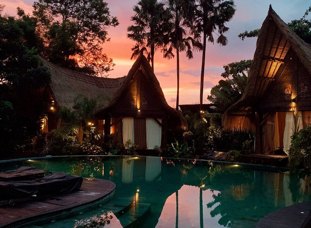 Own Villa sunset colours beyond eco design poolside bedrooms made of recycle iron wood and facing swimming pool surrounded by tropical Bali nature