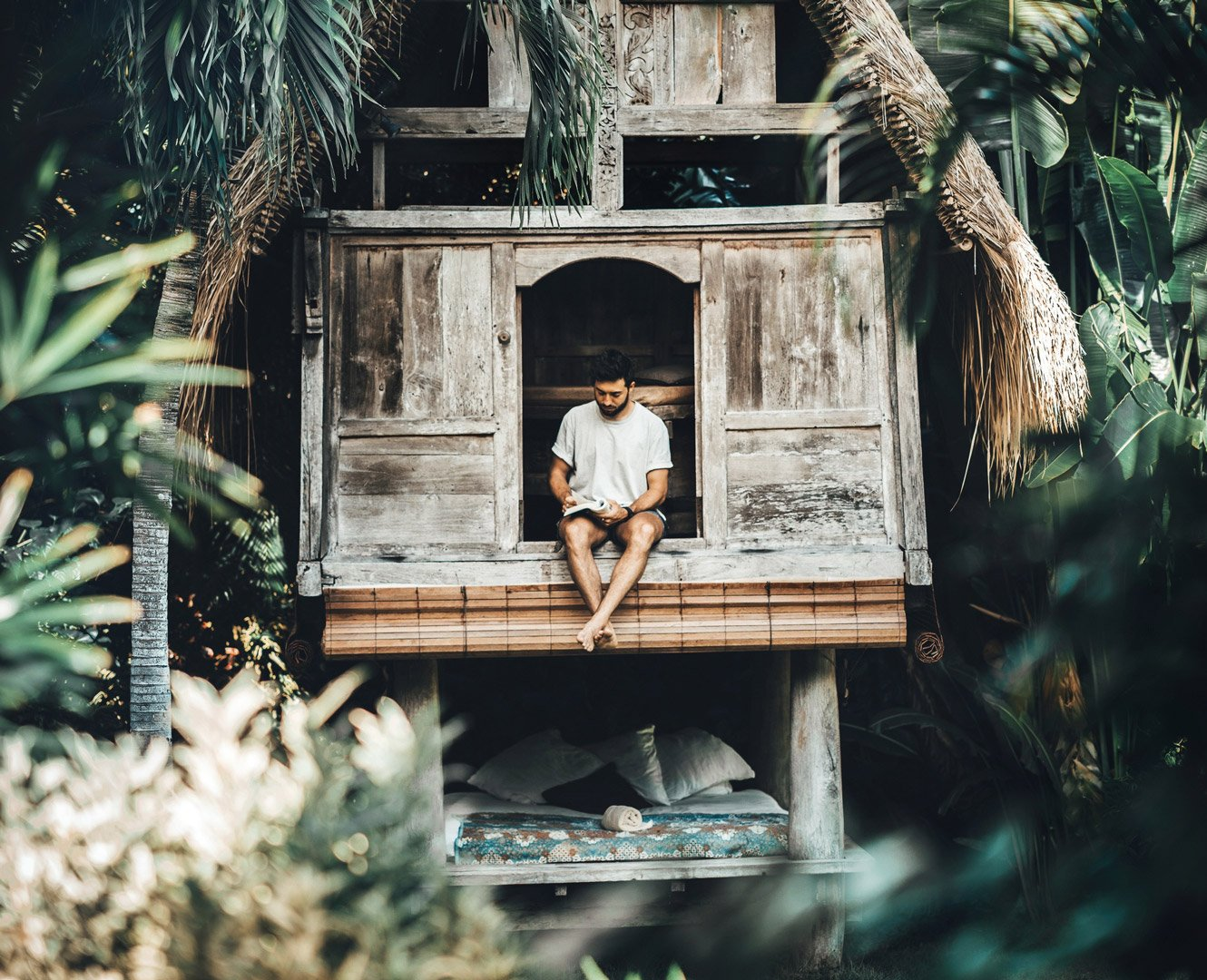 Cozy reading treehouse at Own Villa eco design wooden hut surrounded by palms and green Bali nature