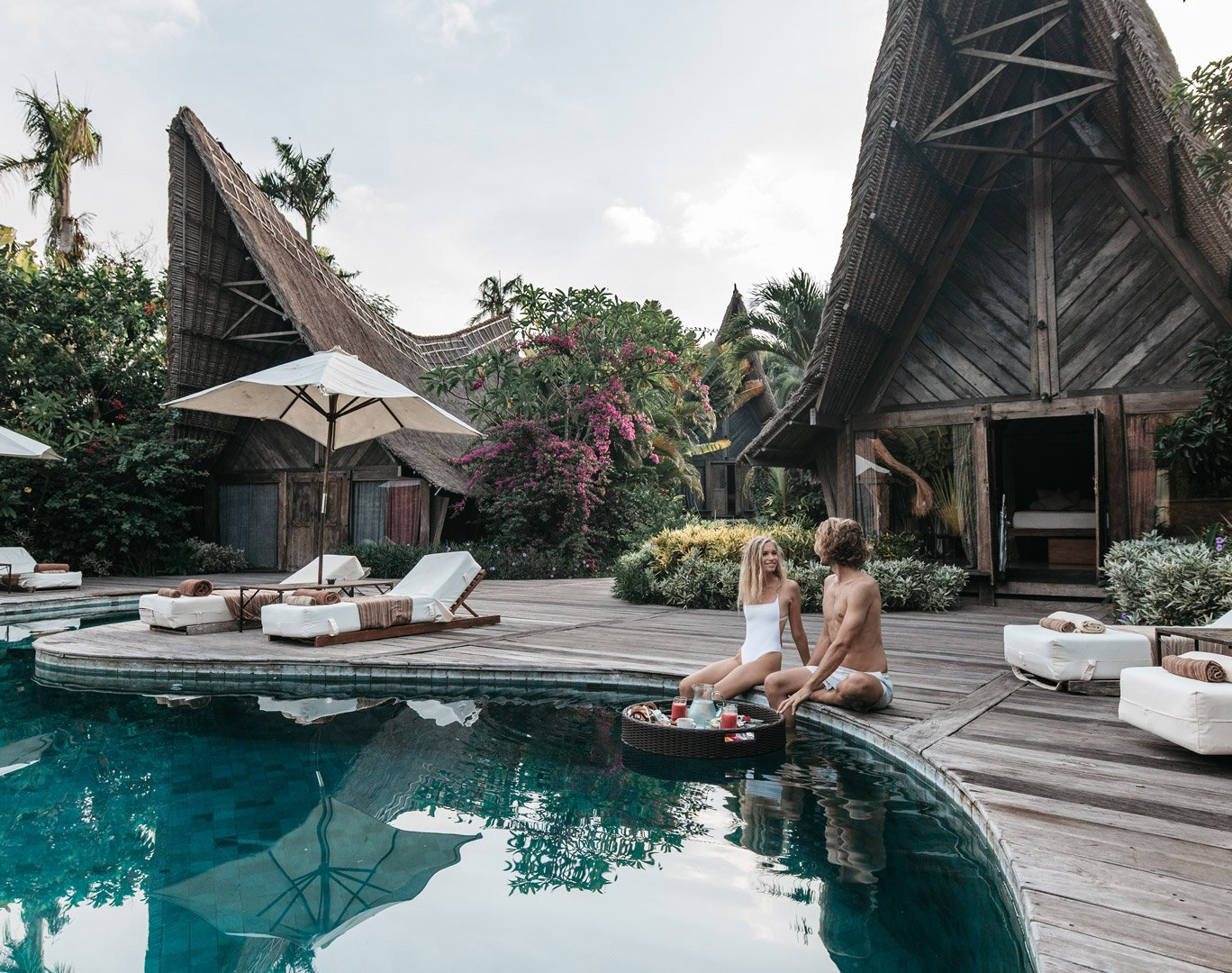 Lovers enjoying their deliciously fresh floating breakfast at Own Villa next to their poolside eco design bedrooms made of recycled iron wood and surrounded by tropical Bali nature