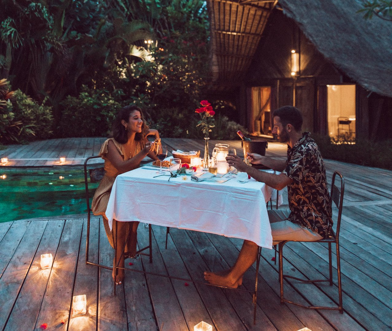 Lovers celebrating their honeymoon with romantic candlelit poolside dinner with roses at Own Villa Bali next to their pool facing eco design bedrooms made of recycled Indonesian iron wood